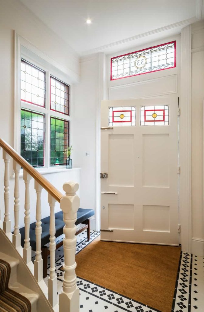 This foyer features a black tufted bench next to the staircase covered in striped runner along with a white front door that blends in with the walls. It is fitted with stained glass panels complementing the transom window.