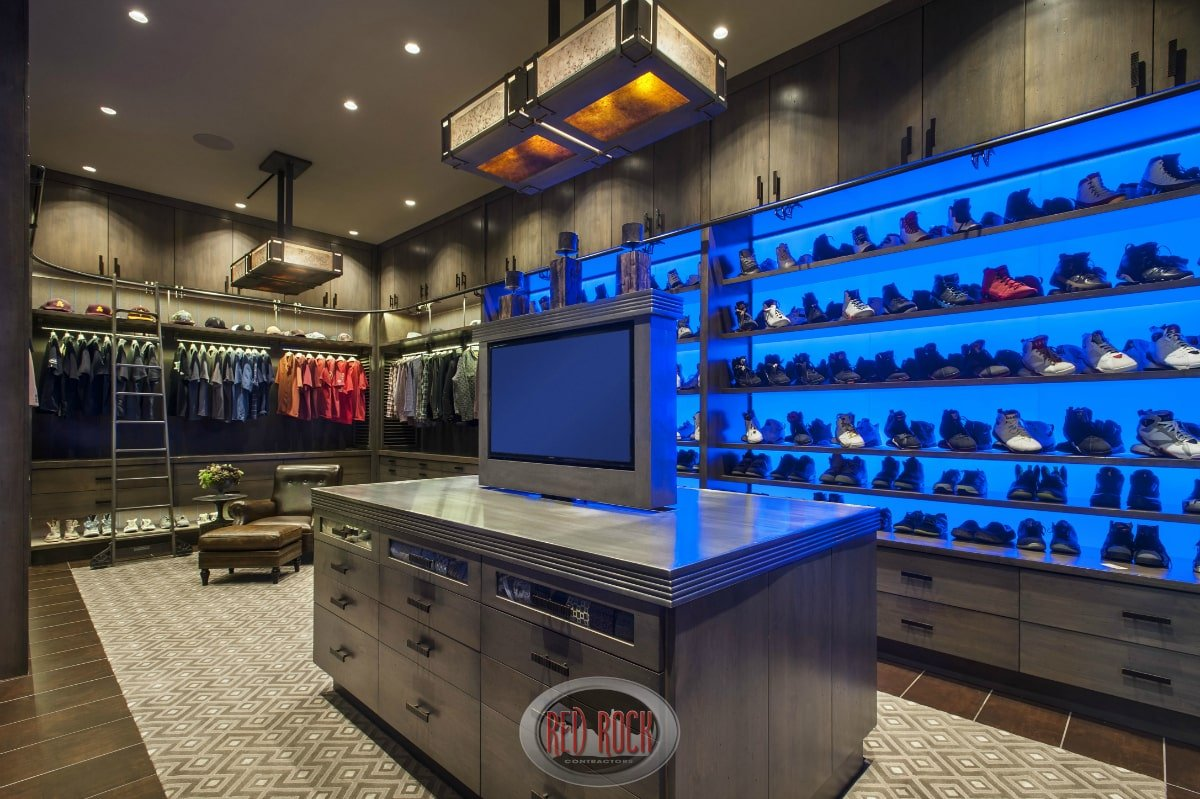 You can tell that this is a man's walk-in closet by how the shoe racks dominate the clothes wardrobe. There's additional storage through the dark wood island in the middle that's complemented by a leather lounge chair.