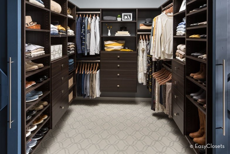A blue double door opens to this walk-in closet with patterned carpet flooring and floating storage in dark wood that are fixed against the gray walls.