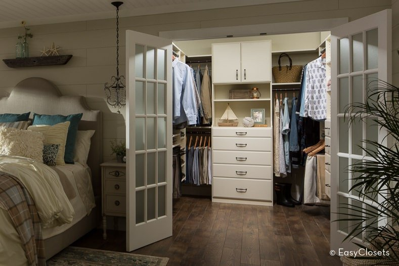 A walk-in closet situated next to the gray upholstered bed showcasing wide plank flooring and a French door that matches the white cabinets and shelves.