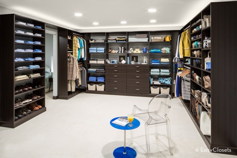Spacious walk-in closet with full height storage and a glass armchair paired with a blue side table that stands out against the beige carpet flooring. It is illuminated by stripped and recessed lights fitted on the regular white ceiling.
