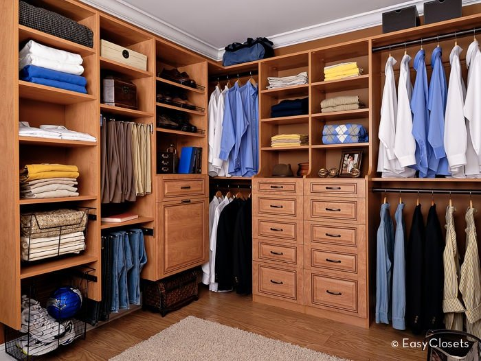 Men's walk-in closet features wooden cabinets and shelves that blend in with the paneled walls and hardwood flooring. It is complemented by a brown shaggy rug that brings an added warmth in the room.