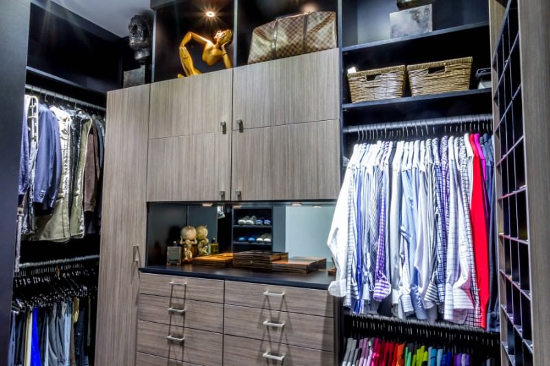 Interesting sculptures add a sleek accent in this walk-in closet with wooden cabinets and black shelving illuminated by recessed lights.