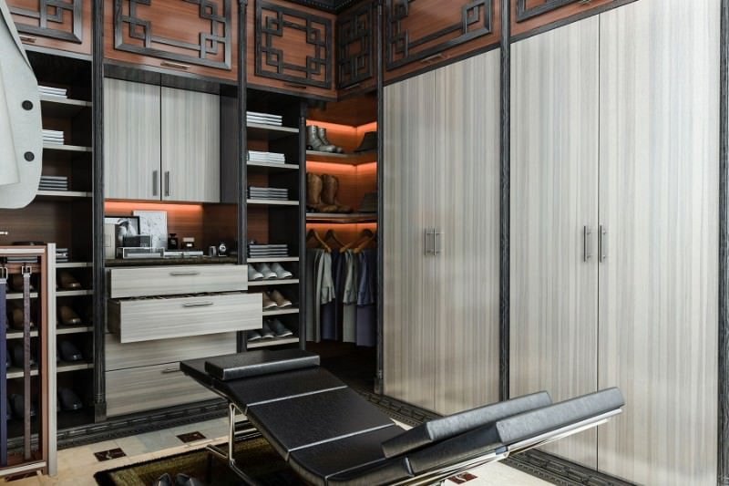 An angled view of the above walk-in closet showcasing a sleek black lounge chair that sits on a bordered rug over marble tiled flooring.