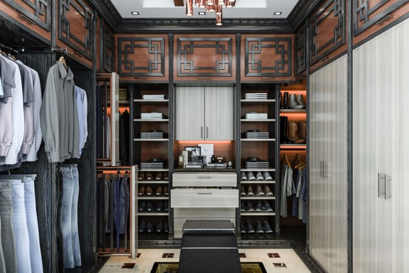 The classic walk-in closet offers open storage and a copper cluster chandelier fixed on the tray ceiling. There are ornate cabinets on top that add character in the room.