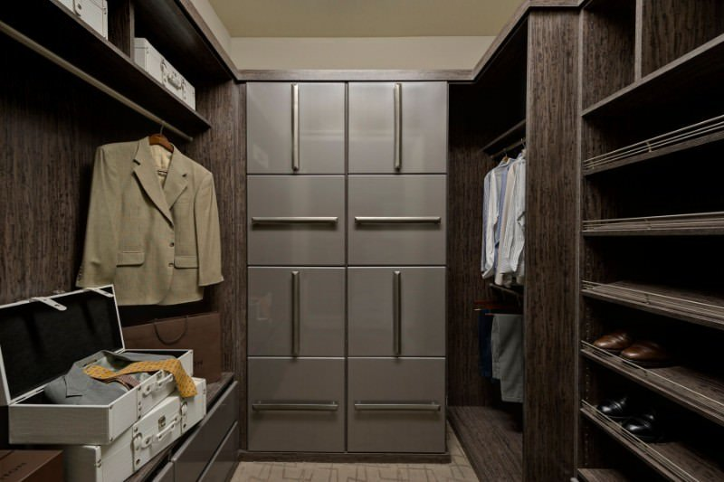 A small walk-in closet filled with dark wood shelving and taupe cabinets in high gloss finish adding subtle contrast for a lighter tone.