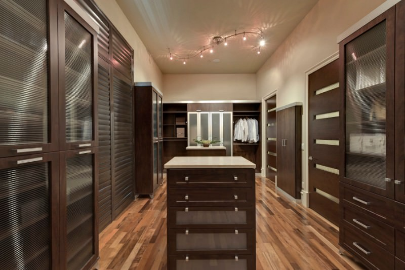 Spacious walk-in closet caters ample storage in dark wood illuminated by track lighting. There are matching islands in the middle that are topped with quartz countertop.