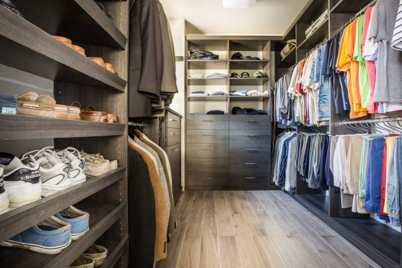 Men's walk-in closet with a galley layout showcasing dark wood storage against the beige walls. It has light wide plank flooring that adds a brighter contrast to the wooden cabinets.