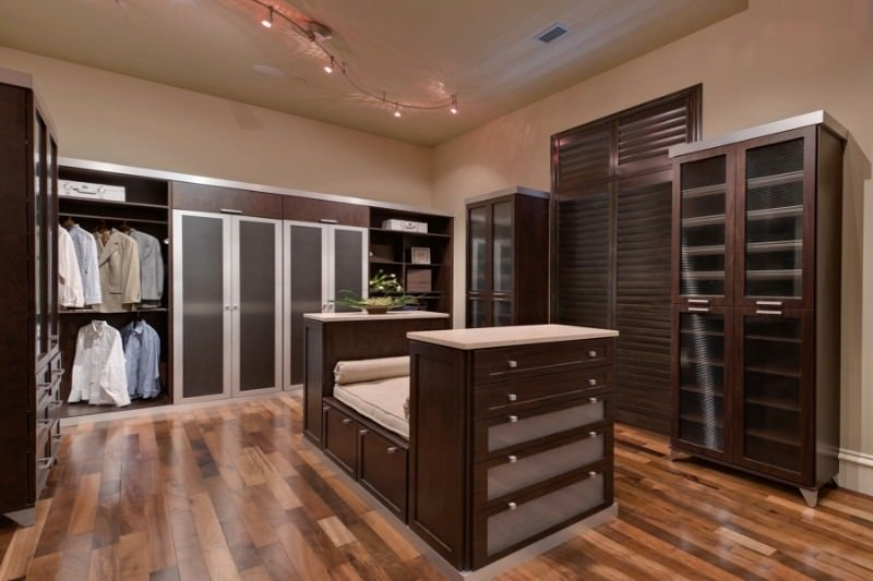 The large walk-in closet features sleek dressers that are integrated with a cushioned seat. It matches the louvered and dark wood cabinets against the beige walls.