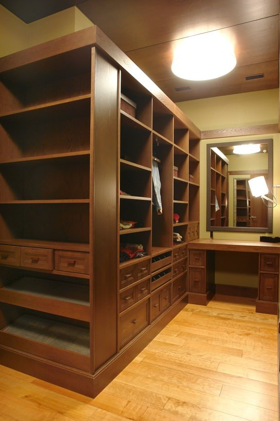 Men's walk-in closet with open shelving and a matching vanity paired with a framed mirror. It is lighted by a wall sconce and a flush light mounted on the wood paneled wall.
