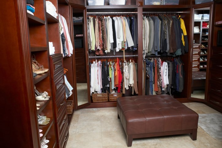 This walk-in closet offers open storage and a pair of full-length mirrors along with a leather tufted ottoman over beige tiled flooring.