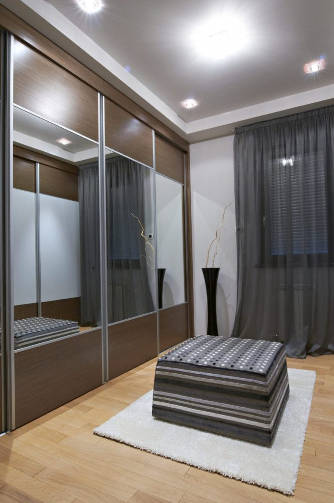 Sleek walk-in closet with a patterned ottoman over a beige shaggy rug along with floor to ceiling cabinets fitted with large mirrors. It is decorated with a tall black vase sitting next to the glazed window that's dressed in a gray sheer curtain.