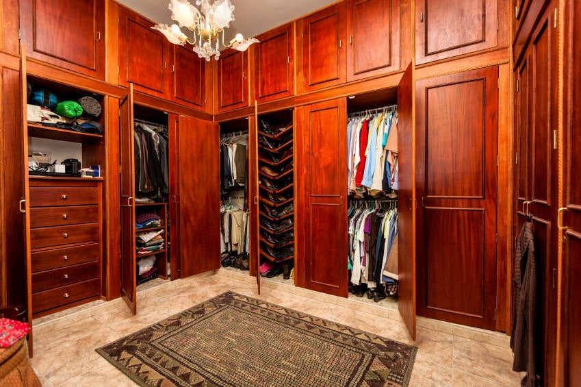 A gorgeous glass chandelier illuminates this walk-in closet boasting rich wood cabinets and a tribal rug that lays on the beige marble flooring.