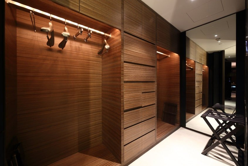 Men's walk-in closet features wooden cabinets complemented by a sleek stool over white flooring. There's a mirrored wall on the side that creates a larger visual space in the area.