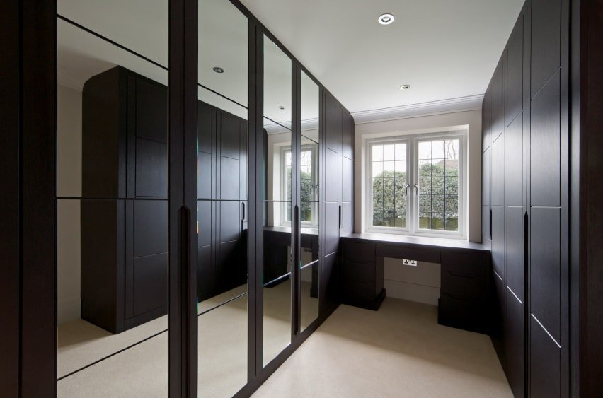 Long and narrow walk-in closet showcases floor to ceiling cabinets with mirrored doors flanking a built-in table underneath the white framed window.