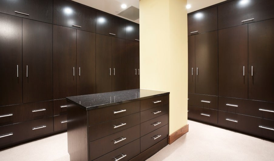 Dark wood cabinets surround a matching island that's fitted with drawers and a black granite countertop. It sits next to the beige pillar that blends in with the carpet flooring.