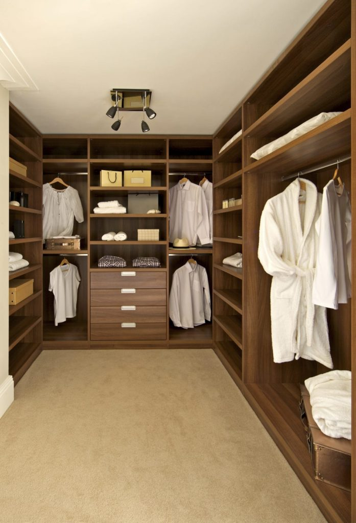 Small walk-in closet with beige carpet flooring and full height storage in dark wood. It is illuminated by black track lights that are fixed on the regular white ceiling.