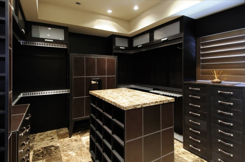 A dark walk-in closet features wooden cabinets and an island with granite countertop matching with the tiled flooring. It includes recessed ceiling lights and a small window covered in roller blinds.