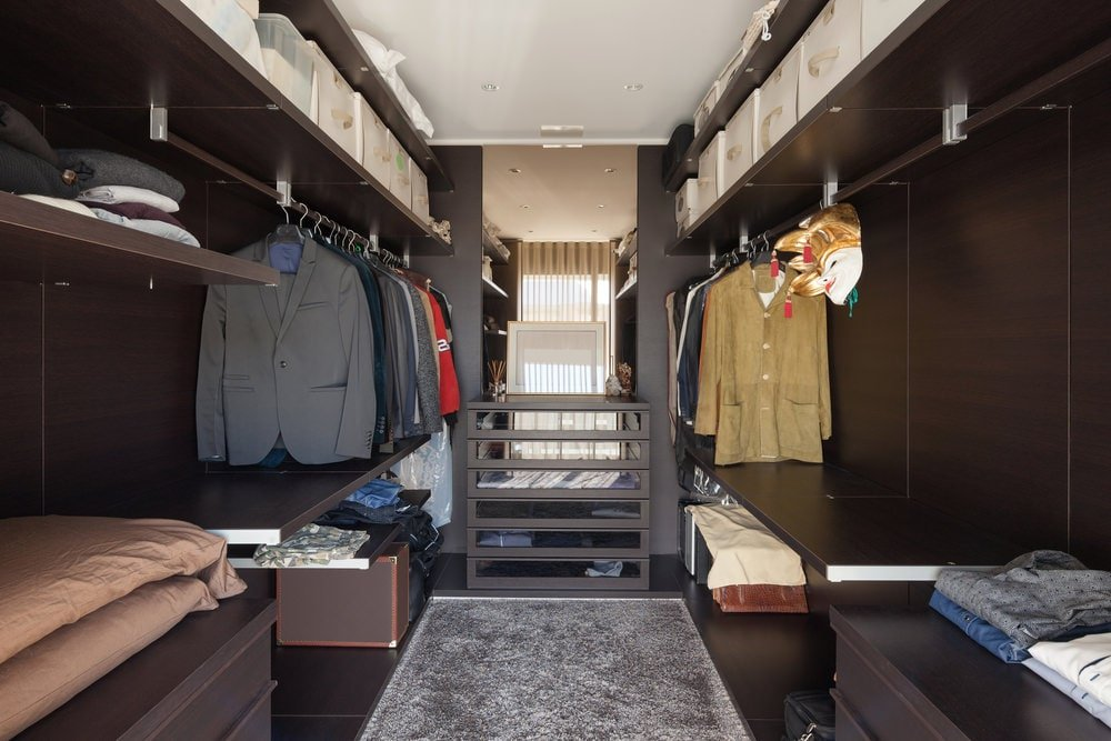 This walk-in closet sports a cohesive look showcasing open shelving in dark wood that matches the paneled walls and hardwood flooring topped by a gray rug. There's a sleek dresser in the middle that's placed against the full-length mirror.