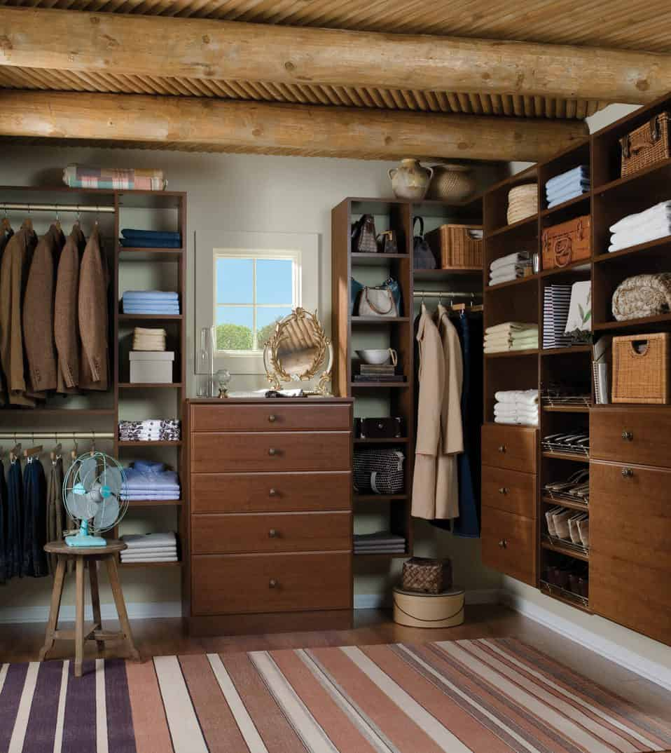Rustic walk-in closet boasts a round stool and a small glazed window above the wooden dresser that's flanked by floating cubbies. It has a wood beam ceiling and hardwood flooring topped by a striped rug.