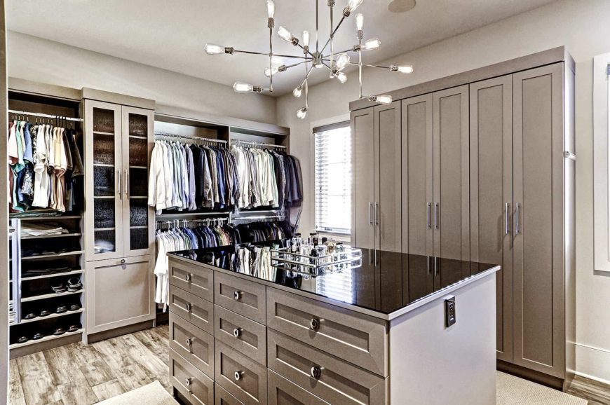 Bright walk-in closet illuminated by a contemporary chandelier that hung over the glass top island. It has wide plank flooring and taupe cabinets that blend in with the concrete walls.