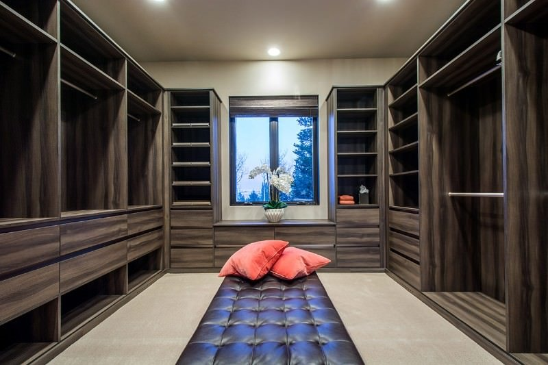 This walk-in closet boasts dark wood cabinets and a black tufted bench accented with coral pillows. It has beige carpet flooring and a glazed window inviting natural light in.
