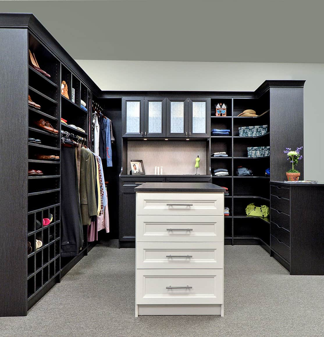 Modular black cabinets along with granite countertop add a striking contrast to the white island that's fitted with drawers and chrome pulls. This walk-in closet has gray walls that blend in with the carpet flooring.