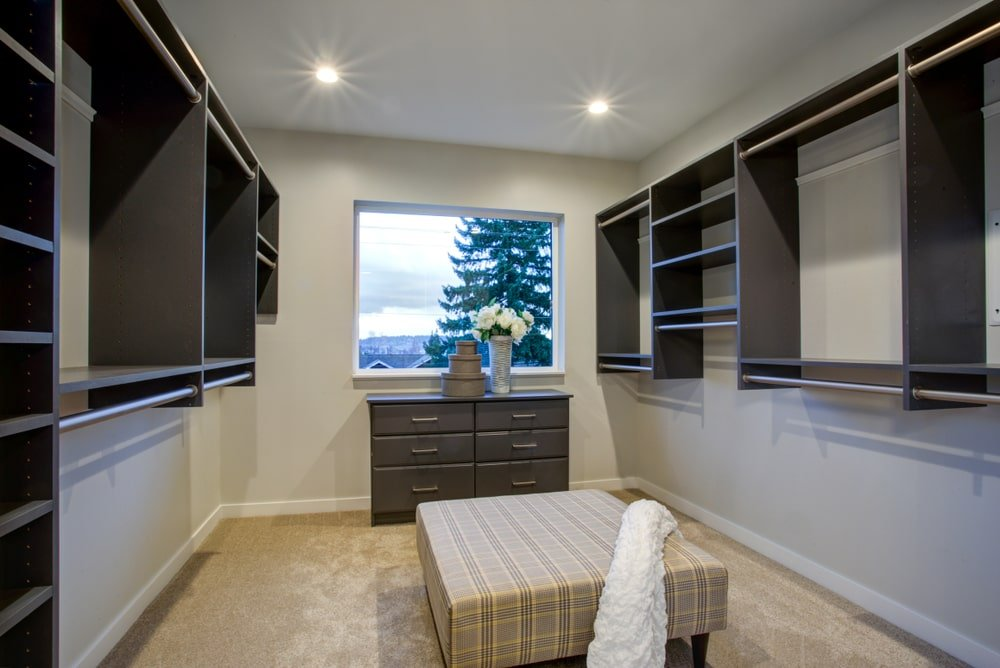 Well-lit walk-in closet boasts floating shelving and a dark wood dresser by the picture window framing the outdoor scenery. It is complemented by a plaid ottoman that's topped with a white throw.