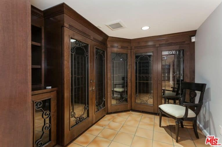 The sophisticated walk-in closet offers wooden cabinets that are fitted with full-length mirrors inlaid with ornate metal borders. It is complemented by a cushioned armchair over terracotta flooring.