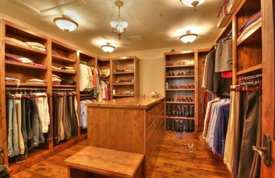 Wooden cabinets run throughout this walk-in closet boasting plenty of semi-flush mount lights along with a vintage chandelier that hung over the wooden dresser.