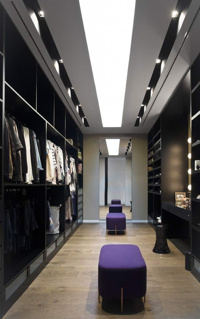 A pair of purple ottomans bring a pop of color in this modern walk-in wardrobe with black cabinetry and a built-in vanity paired with a sleek round stool. It is illuminated by track lights and a skylight that runs the length of the room.