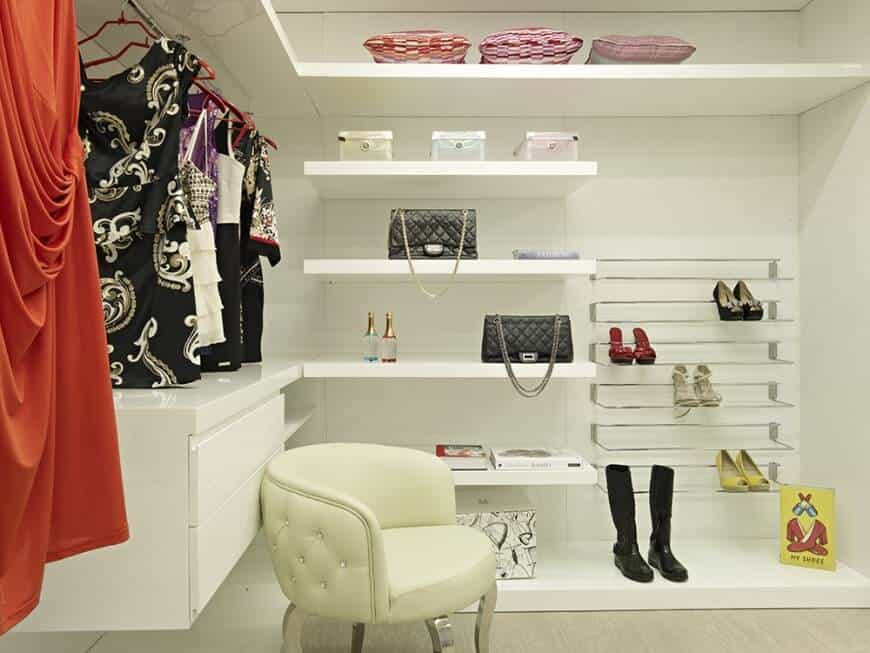 Simple walk-in closet with open storage showcasing floating shelves and drawers along with stainless steel shoe rack. It is complemented by a tufted round back chair over the light hardwood flooring.
