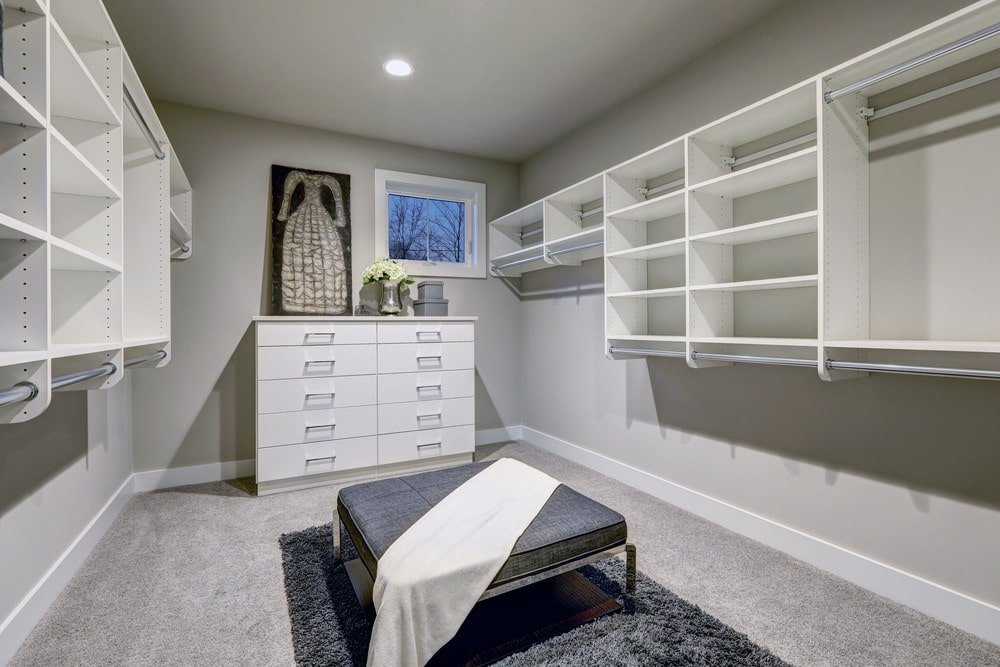 This walk-in closet is decorated with a gorgeous dress painting that sits on a white dresser over carpet flooring. There's a gray ottoman in the middle that's surrounded by floating open shelves fitted with wardrobe poles.