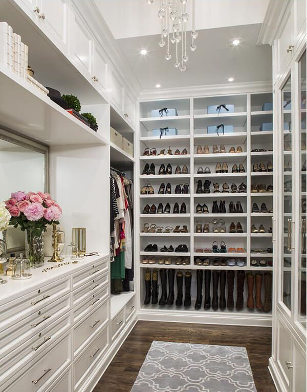 Narrow walk-in wardrobe with full height storage and a gray patterned rug that lays on the dark hardwood flooring. It is illuminated by a crystal chandelier and recessed ceiling lights.