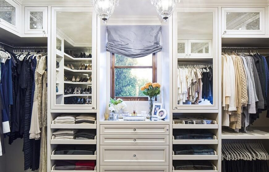 Mirrored closet doors and pull-out drawers flank a wooden framed window that's covered in a gray roman shade. It is fixed above a dresser that's topped with vases and framed photos.