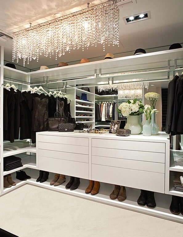 A linear crystal chandelier adds a touch of elegance in this walk-in closet that's decorated with a framed photo and various shaped vases.