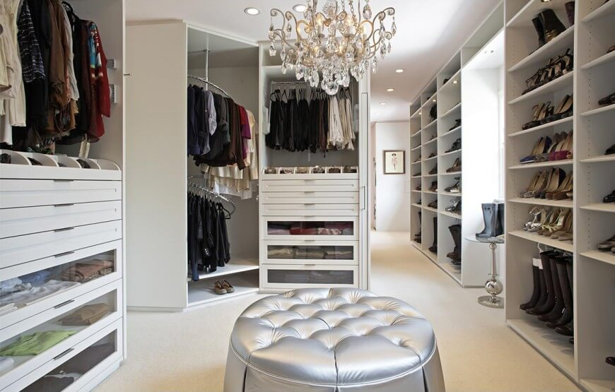 A large walk-in closet with white modular wardrobe cabinets and a silver tufted ottoman over beige carpet flooring. It is illuminated by a glam crystal chandelier and recessed ceiling lights.