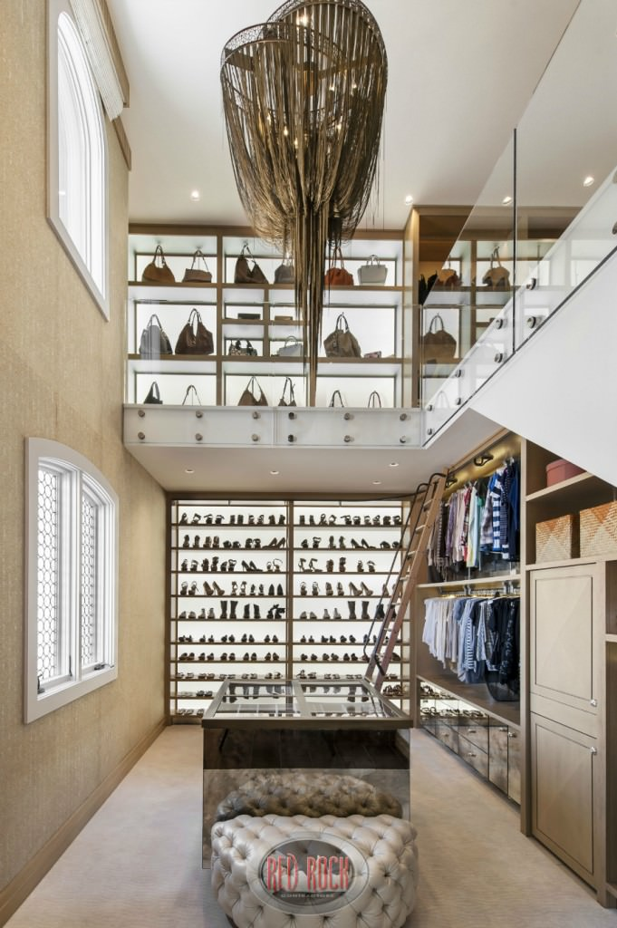 A large eccentric chandelier illuminates this two story walk-in wardrobe with display cabinets and a mirrored island complemented by a classy tufted seat. It has beige carpet flooring and glazed windows inviting natural light in.