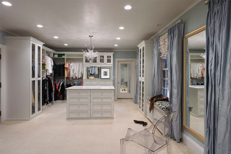 Spacious walk-in wardrobe with beige carpet flooring and white framed windows dressed in blue draperies that blend in with the walls. It includes a glass chair and a seat nook along with a white island lighted by a crystal chandelier.