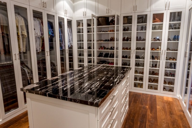 A natural hardwood flooring adds warmth in this walk-in closet with glazed wardrobe doors and a white island contrasted by black marble countertop.