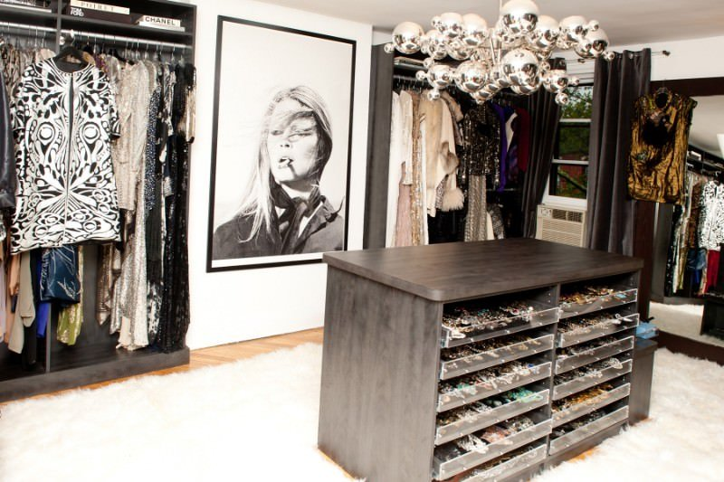 This walk-in wardrobe is decorated with a chrome chandelier and a lovely portrait flanked by dark wood cabinets. It is accompanied by a full-length mirror and an island that's surrounded by white faux fur rugs.