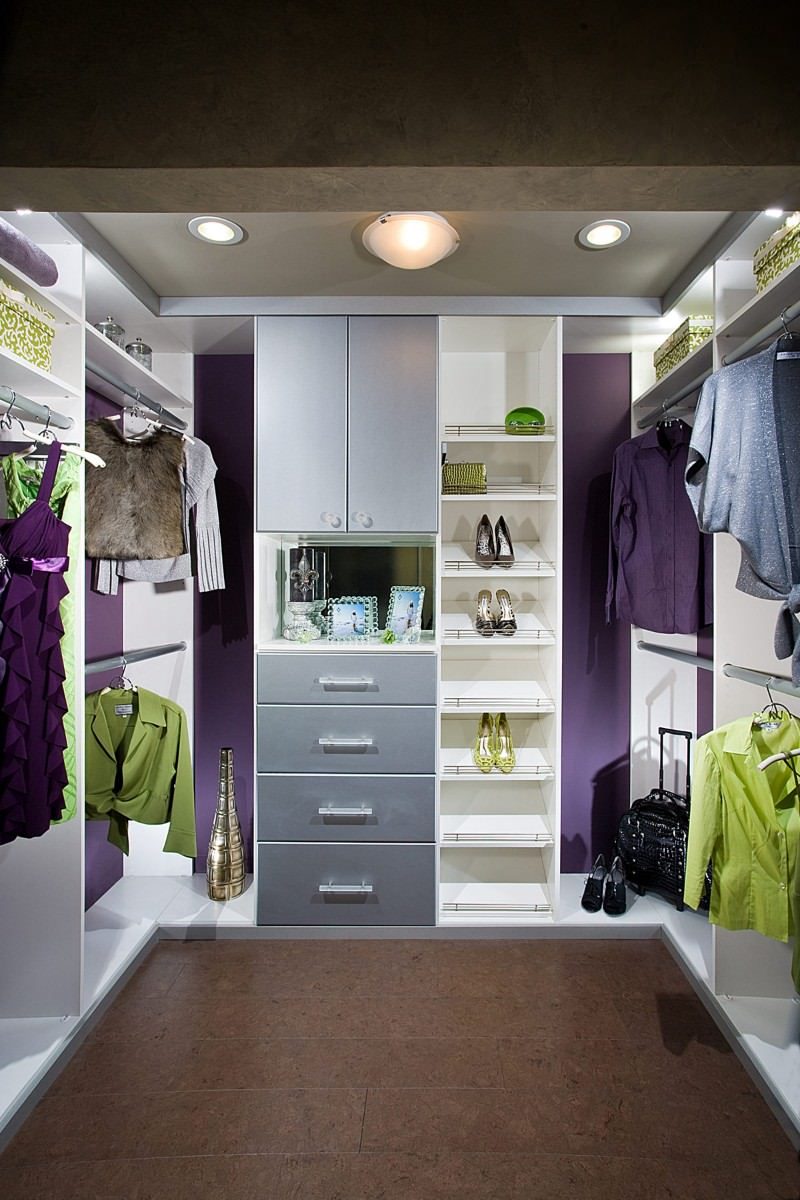 Purple walls add a pop of color in this walk-in closet with wide plank flooring and a tray ceiling mounted with flush and recessed lights.
