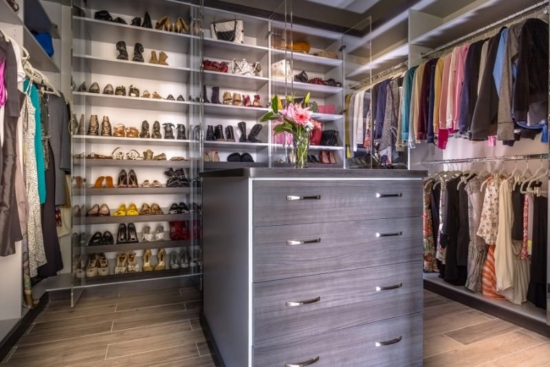 A gray counter topped with a glass flower vase is the focal point in this walk-in closet with an open wardrobe and a modular shoe rack in the middle enclosed in glazed doors.