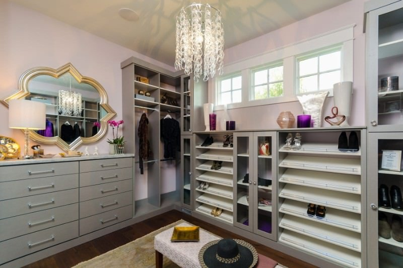 A stylish brass framed mirror adds a nice accent in this well-lit walk-in wardrobe featuring light gray cabinets and a glass chandelier that hung over the cushioned bench.