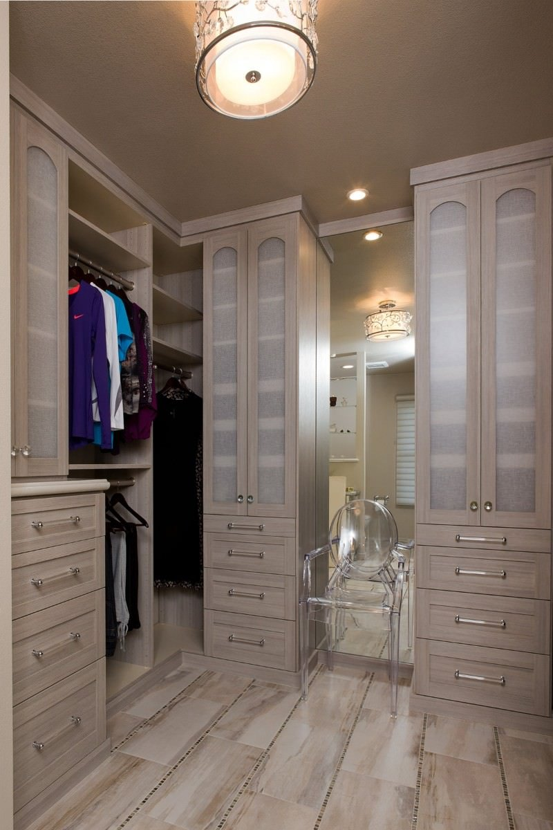 A lovely drum chandelier illuminates this walk-in wardrobe showcasing light wood cabinets and a glass round back chair placed against the mirrored wall.