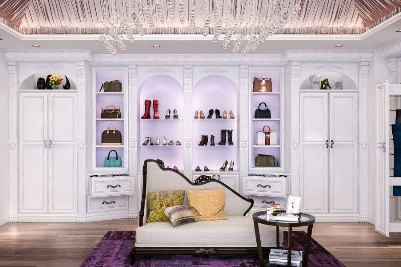 Elegant walk-in closet with natural hardwood flooring and a canopy ceiling mounted with a trendy crystal chandelier. It includes white cabinets and a classy chaise lounge paired with a round coffee table over a purple velvet rug.