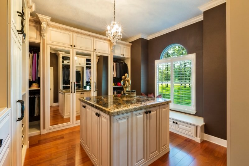 The warm walk-in wardrobe boasts mirrored closet doors and a granite top island lighted by a candle chandelier. It includes a built-in bench with storage by the white framed window overlooking the outdoor greenery.