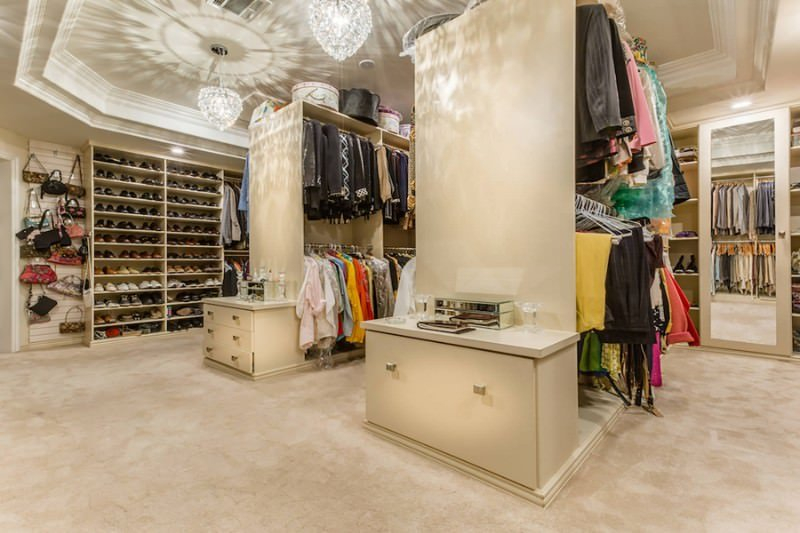 Spacious walk-in closet illuminated by gorgeous crystal chandeliers that hung from the tray ceiling. It offers ample storage and a pair of counters housing the accessories.