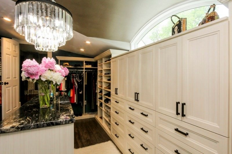 Wrought iron hardware along with a black marble countertop provides a striking contrast to the white cabinets and island that's lighted by a cascading chandelier.