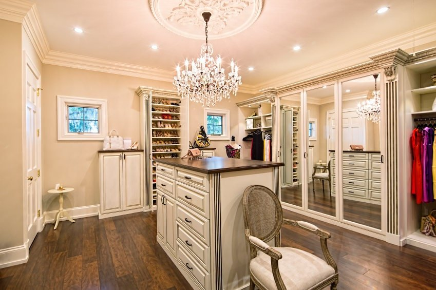 A classy walk-in wardrobe offers ample storage and mirrored closet doors along with a round back chair that sits next to the wood top island. It is illuminated by a fancy crystal chandelier and recessed ceiling lights.